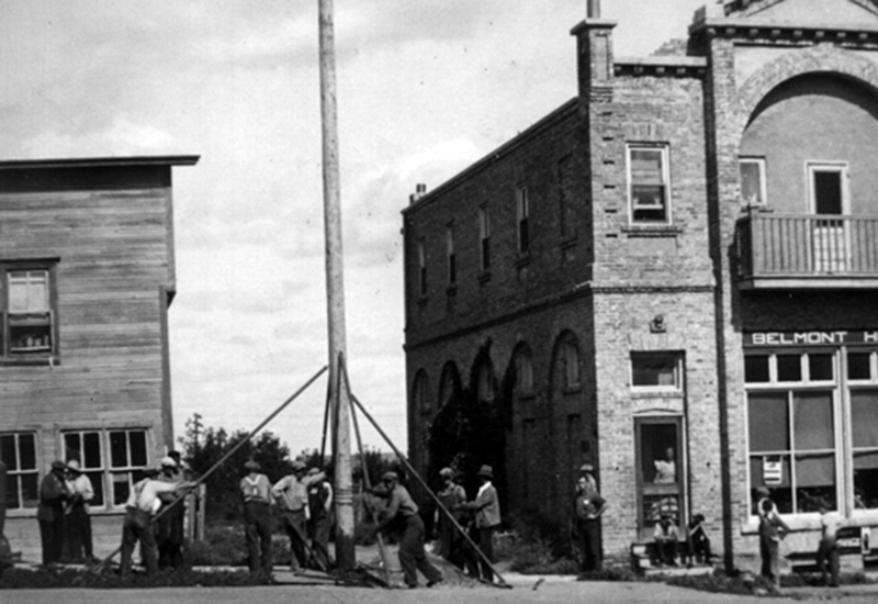 Photo of workers erecting a wooden hydro pole beside the Belmont Hotel while townspeople look on.