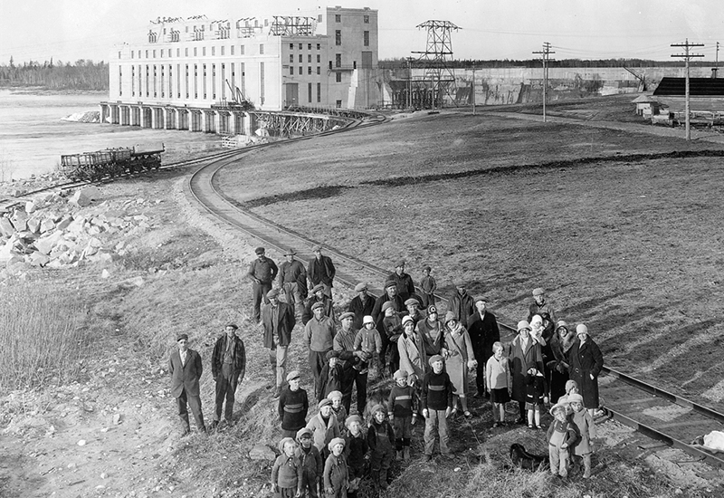 Photo of employees, their spouses, and children stand beside the railway line outside of Great Falls GS. The generating station is in the background.