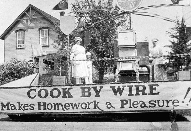 Photo of a parade float in Carman with three people in chef hats and aprons showing off an electric stove. The banner reads: Cook by wire makes homework a pleasure!