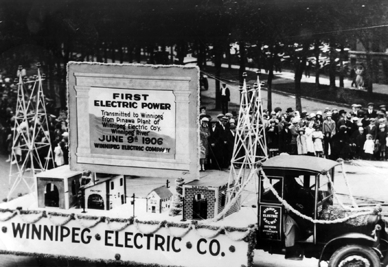 Photo of a Winnipeg Electric Co. parade float driving past crowds. The float is made up of buildings and transmission towers celebrating the Pinawa to Winnipeg transmission.