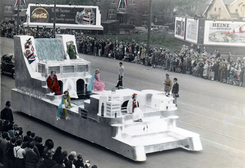 Photo of people in fancy costumes sitting on a parade float representing a hydroelectric dam and a city that receives its electricity. People line both sides of the street.