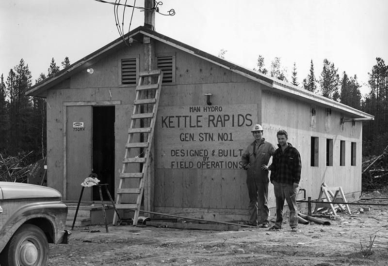 Photo of two men stand beside the rough-built office of Kettle Field Operations.