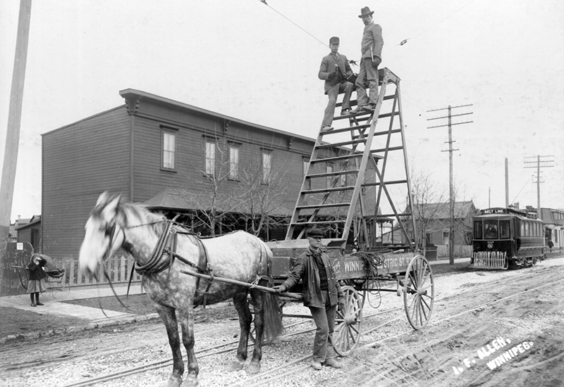 Photo of two men sitting on a tall ladder that is built on a platform of a horse-drawn cart.